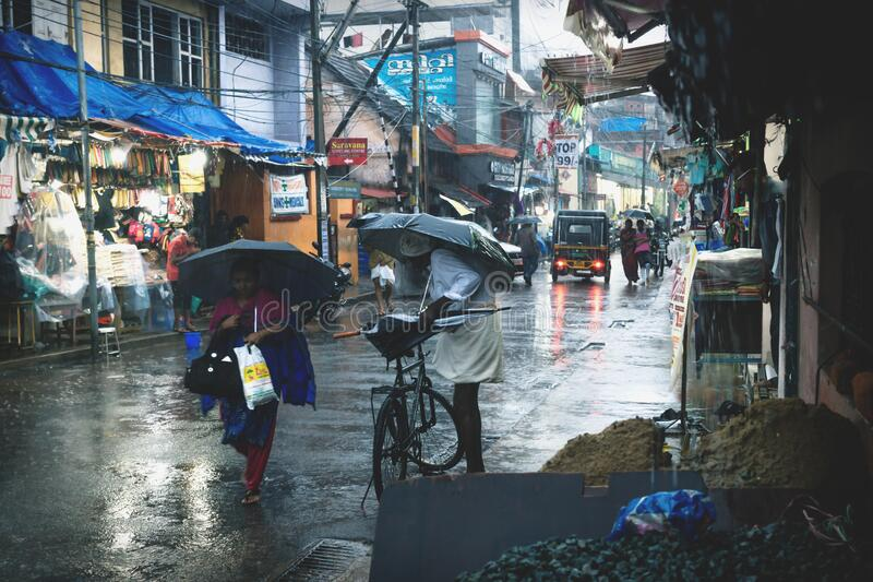 Local Indian people on a shopping street during heavy rain in Thiruvananthapuram, Kerala, India. Thiruvananthapuram, Kerala, India - 30 November 2017: Local stock images