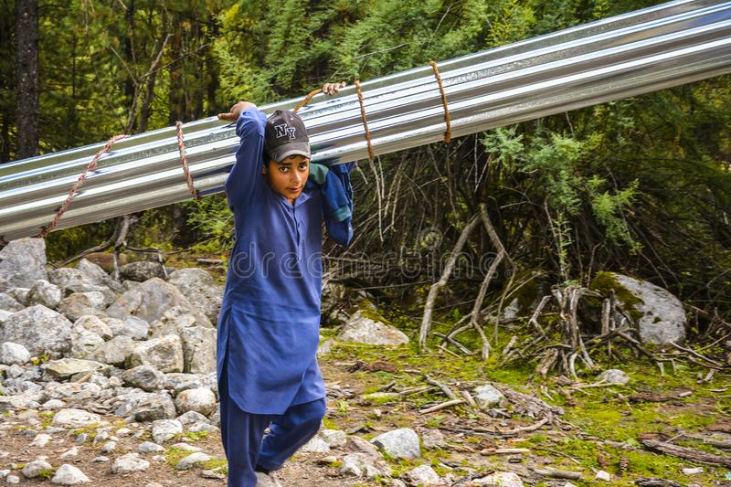 A local kid carrying metal roof sheets stock images