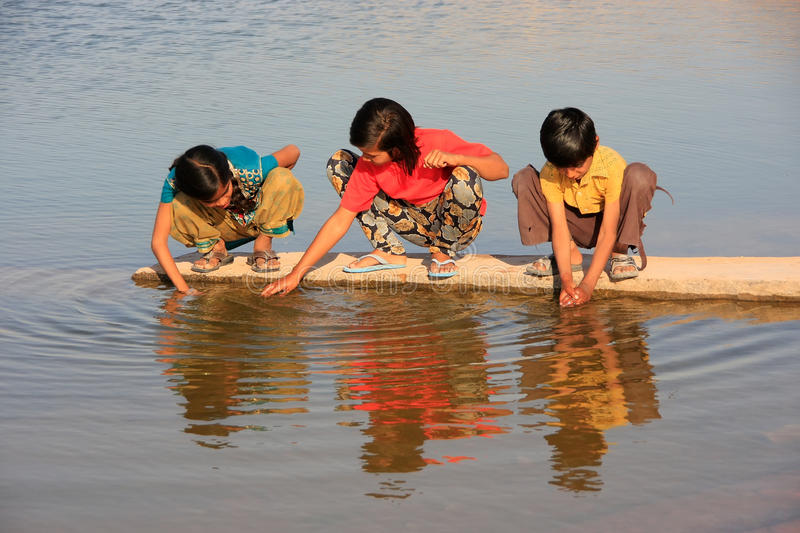 Local kids drinking from water reservoir, Khichan village, India. Local kids drinking from water reservoir, Khichan village, Rajasthan, India royalty free stock photography