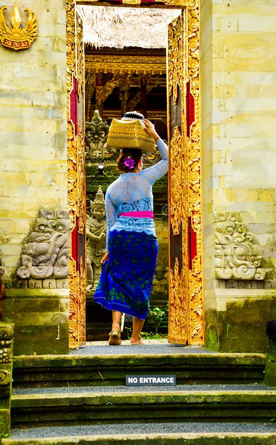 A Balinese woman wearing traditional local clothing entering a sacred temple royalty free stock images