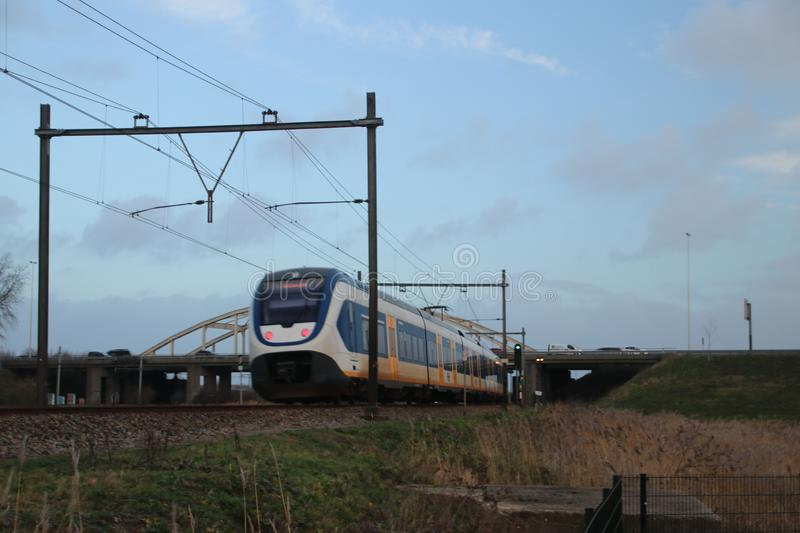 Local light rail communter train type SLT at railroad track between Gouda and The Hague at Moordrecht crossing. stock photo