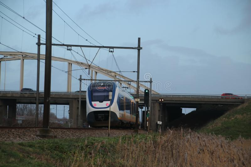 Local light rail communter train type SLT at railroad track between Gouda and The Hague at Moordrecht crossing. stock photography