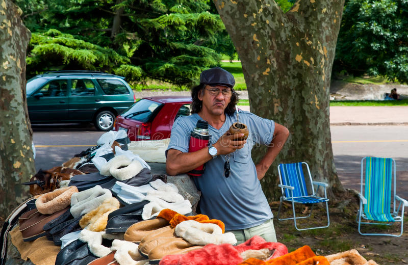 Local market in Uruguay: Street Vendor selling slippers and drink mate royalty free stock photos