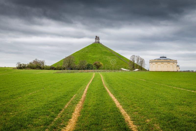 Local memorável do monte do leão famoso no campo de batalha de Waterloo com nuvens escuras, Bélgica fotografia de stock royalty free
