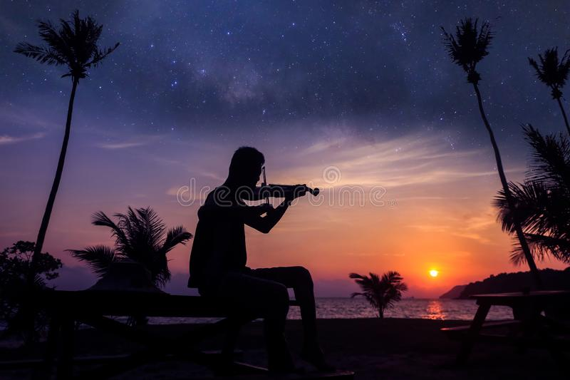 Local musicians, Asian man playing violin on the coconut beach with million stars galaxy. Silhouette artist on purple sky background royalty free stock images