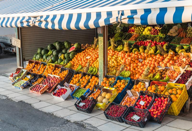 Local neighborhood fresh organic fruit market counters with fresh colorful fruits on display in greece royalty free stock photo