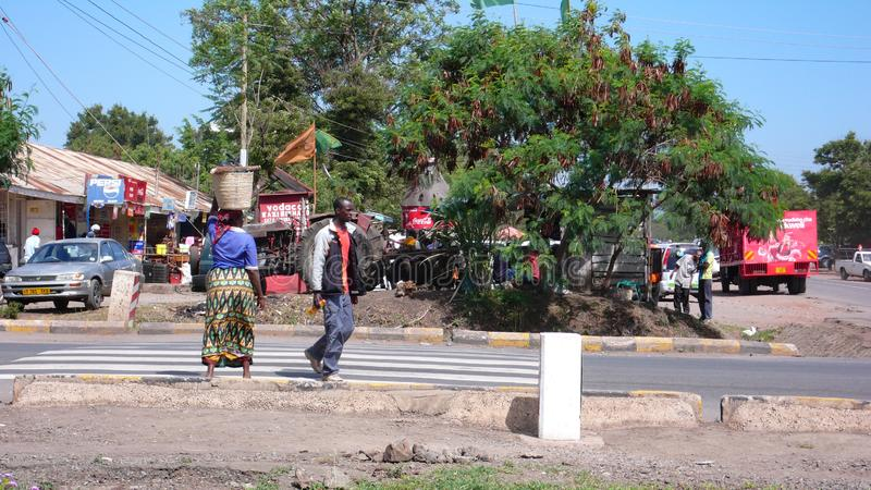 Local people coming from and going to the daily market in the town center of Moshi. Moshi, Kilimanjaro Province / Tanzania: 28. December, 2015: local people royalty free stock photo