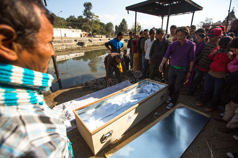Local people during the cremation ceremony along the holy Bagmati River in Bhasmeshvar Ghat at Pashupatinath temple in Kathmandu. KATHMANDU, NEPAL - DEC 3, 2013 royalty free stock image
