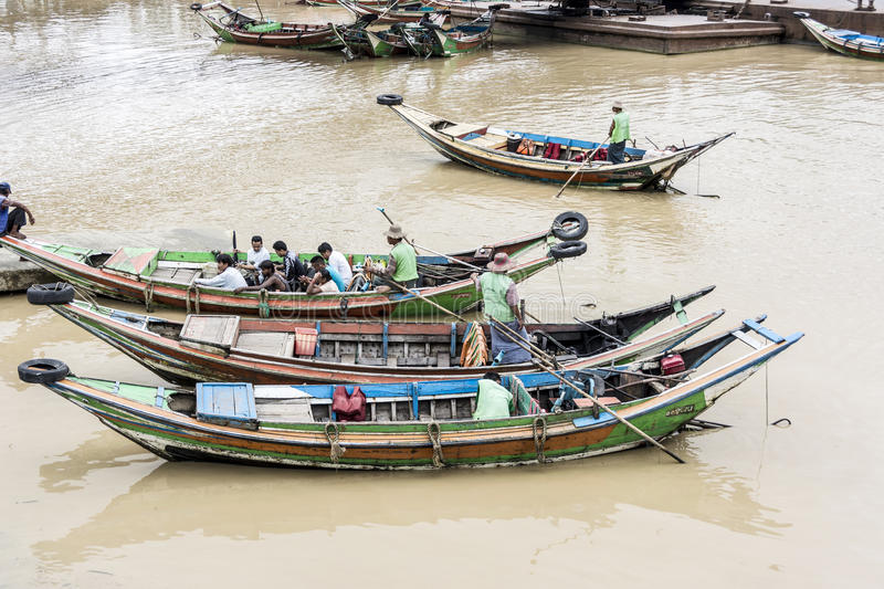 Local people in the typical longboats at the inle lake. NIAUNGSHWE, MYANMAR - AUG 13, 2015: local people in the typical longboats at the inle lake. The ferry royalty free stock photos