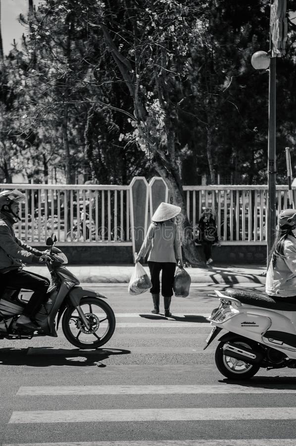 Local people wear Vietnamese hat crossing street with traffic in Da Lat - Vietnam royalty free stock photography