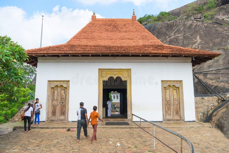Local pilgrims near entrance to Dambulla Golden cave temple comp. DAMBULLA, SRI LANKA - NOV 2016: Local pilgrims near entrance to Golden cave temple complex stock photography