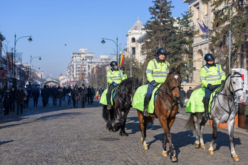 Local police equestrians in green uniform and helmet. IASI, ROMANIA - JANUARY 24, 2018: Happy smiling local police equestrians in green uniform and helmet on royalty free stock images