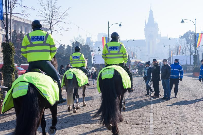 Local police equestrians in green uniform and helmet. IASI, ROMANIA - JANUARY 24, 2018: Local police equestrians in green uniform and helmet on horses patrolling royalty free stock photos