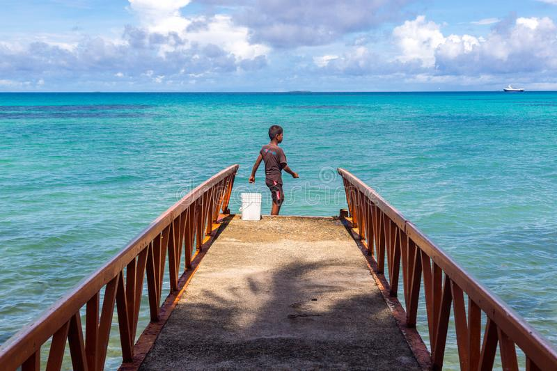A local Polynesian boy fishing from a jetty pier in a tropical azure turquoise blue lagoon, Tuvalu, Polynesia, Oceania. royalty free stock photography