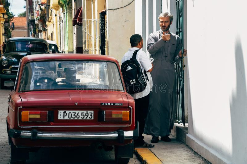 A local priest talks to man in Havana, Cuba. A local priest talks to man next to a red Lada in Havana, Cuba royalty free stock image
