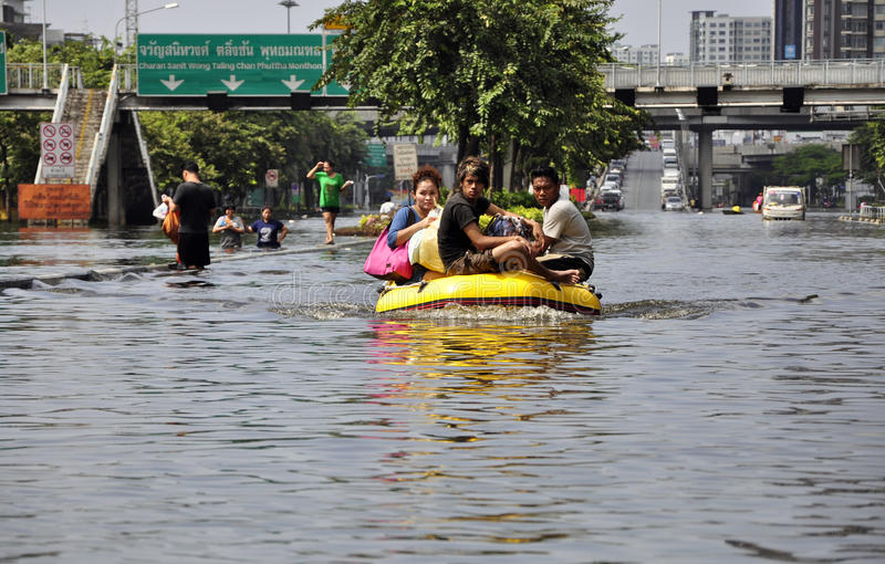 Local residents use inflatable boat. Local residents use an inflatable boat on a thigh-deep section of a flooded road in Bangkok, Thailand, circa 2011 royalty free stock photo