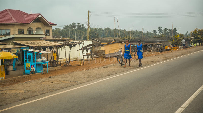 Local residents are walking along the street in Cape Cost. Cape Cost, Ghana - July 30, 2014: Local residents are walking along the street in Cape Cost in Ghana royalty free stock photo