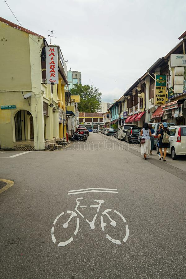 Local road in George Town showing bike direction lane sign on street surface with traditional heritage sino-portuguese shophouse, royalty free stock photo