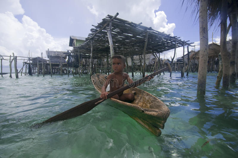 A local sea gypsy kid paddles a boat stock photography