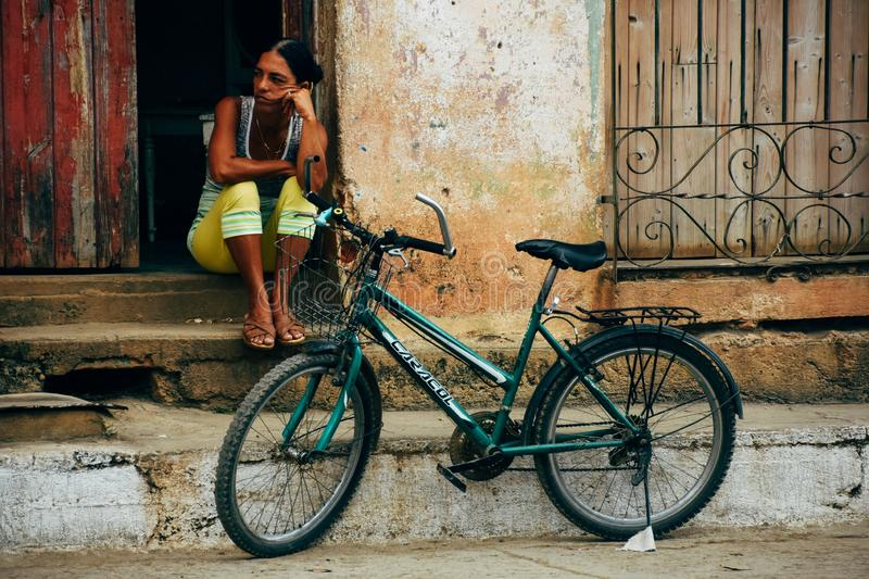A local sits on her door step and looks down the street in Trinidad, Cuba. A local sits on her door step and looks down the street and relaxes in Trinidad, Cuba royalty free stock images