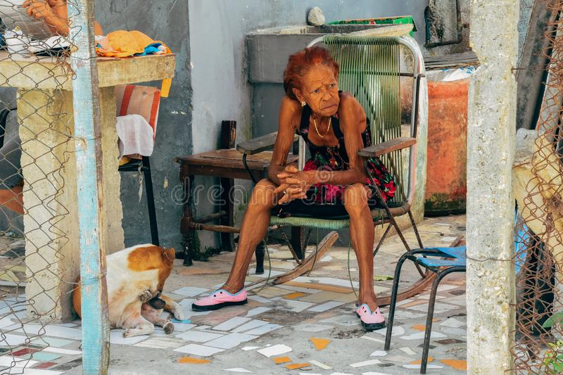 A local sits in the shade in Havana, Cuba. A local sits in the shade with her dog in Havana, Cuba royalty free stock photography