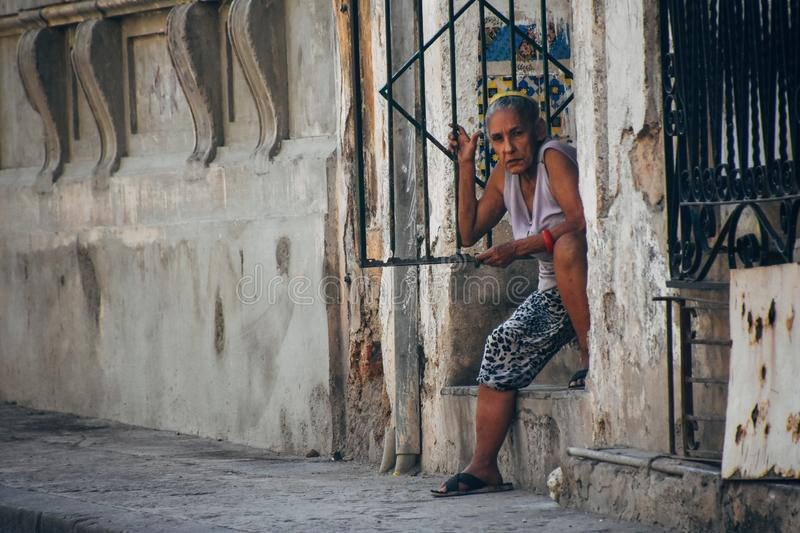 A local sits in the shade in Havana, Cuba. A local sits in the shade in their front door in Havana, Cuba royalty free stock image