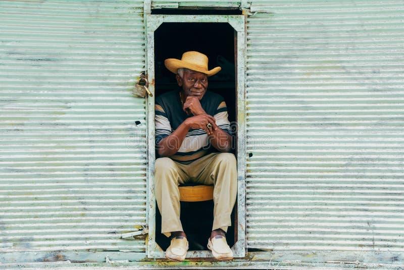 A local sits in a tight spot in Havana, Cuba. A well dressed local sits in a tight spot in Havana, Cuba stock photo