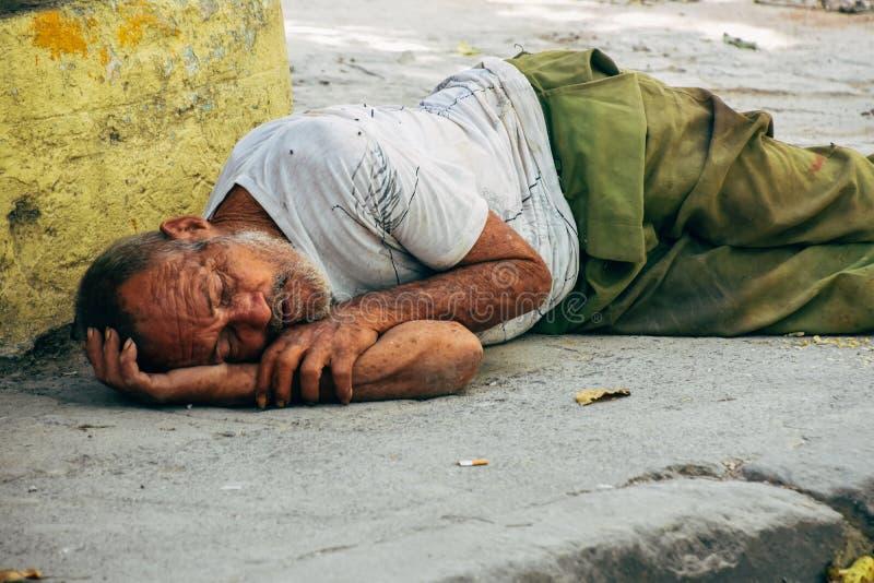 A local sleeps on the sidewalk in Havana, Cuba. A tired local sleeps on the sidewalk in Havana, Cuba stock photos