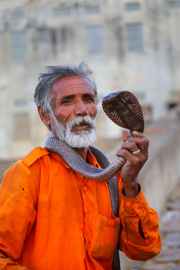 Local snake charmer holding Indian cobra in the street of Jaipur. India. Jaipur is the capital and largest city of the Indian state of Rajasthan royalty free stock image