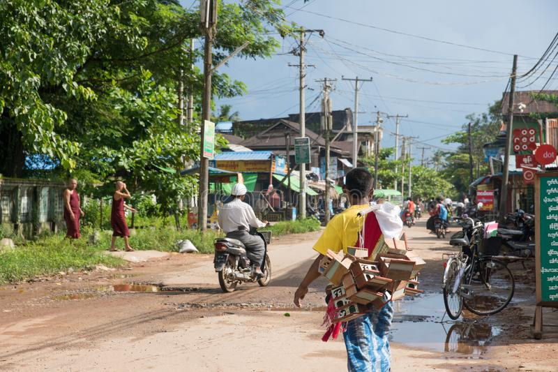 Local street scene in bago myanmar, man carrying wooden toys royalty free stock images