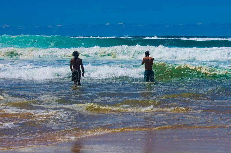 Local Surfers. This Australian beach has quite wild surf and is known for its dangerous rips. These two boys are local surfers and know how to read the surf and royalty free stock photography