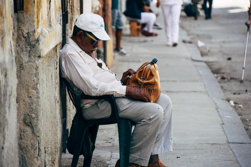 A local takes a nap in the shade in Havana, Cuba. A local takes a nap and relaxes in the shade in Havana, Cuba stock image