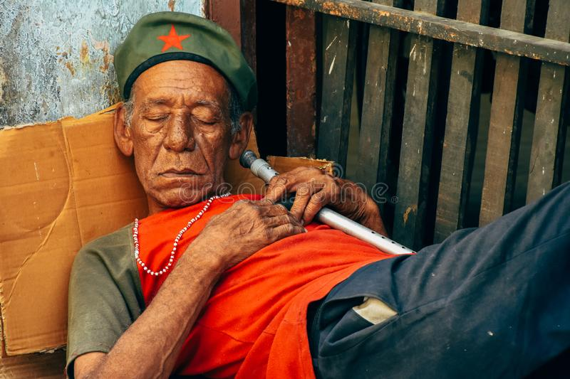 A local takes a nap in the shade in Havana, Cuba. A local takes a long nap in the shade in Havana, Cuba stock photography