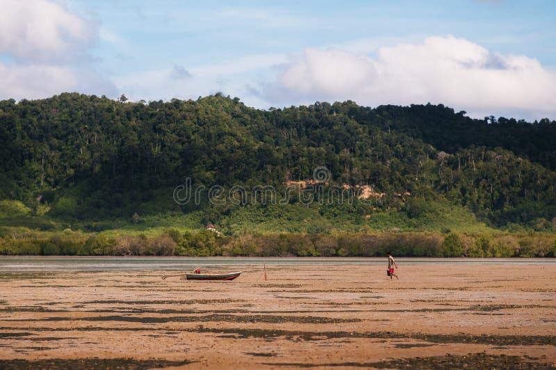 Local Thai guy with fishing boat on muddy land of Tung Yee Peng, Koh Lanta island, Krabi, Thailand stock image