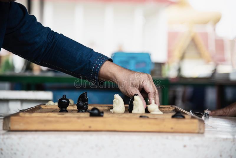 Local Thai people play old traditional Thai chess in public area. Slow life style local people with chess board game concept stock images