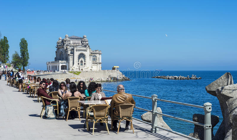 Local and tourists enjoying food restaurants near Casino. CONSTANTA, ROMANIA - MAY 01, 2014: Local and tourists enjoying eating on shore of Black Sea with sight stock photos