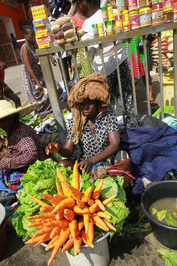 A local trader with a makeshift stall of vegetables at a street market in Accra, Ghana. A local trader with a makeshift stall of fresh, raw, organic vegetables royalty free stock photos