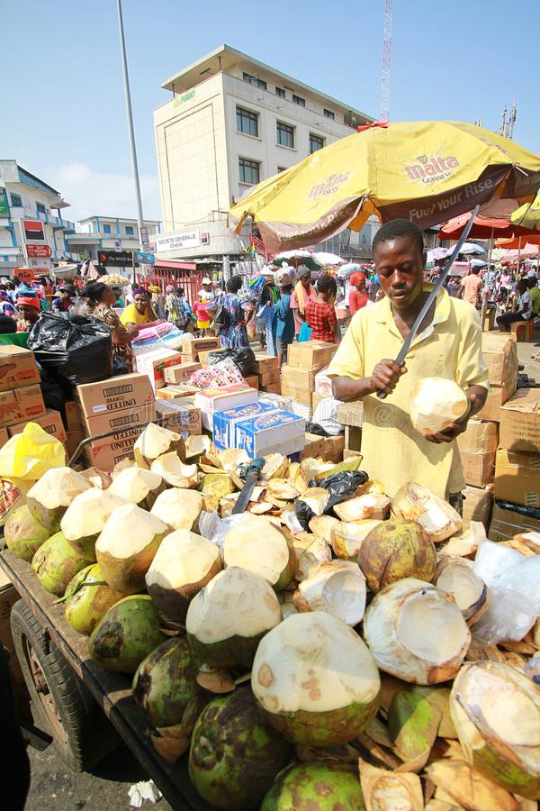 A local trader selling coconuts at a street market in Accra, Ghana. A local trader selling juicy, raw, fresh, organic coconuts at a street market in the city of stock photography