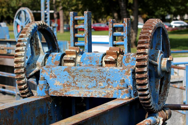 Local unused small dam cogwheel rusted gear with cracked dilapidated paint mounted on metal beam with strong bolts. On warm sunny day stock photo