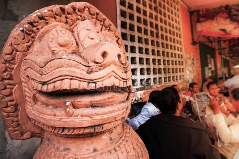 A local urban cafe and a statue of Khmer Singha on the sidewalk of Phnom Penh City, Cambodia stock photography