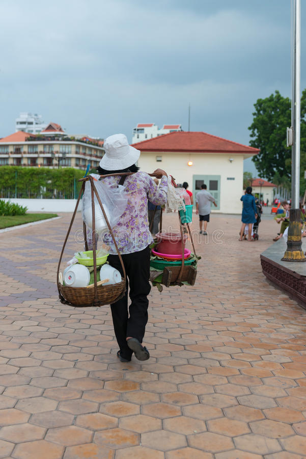 Local vendor carrying street foods on a shoulder mounted rack. royalty free stock photos