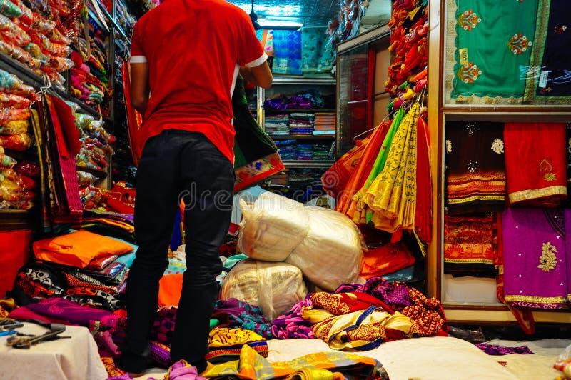 A vendor sells silk in Varanasi, India. A local vendor sells silk scarfs in Varanasi, India royalty free stock image