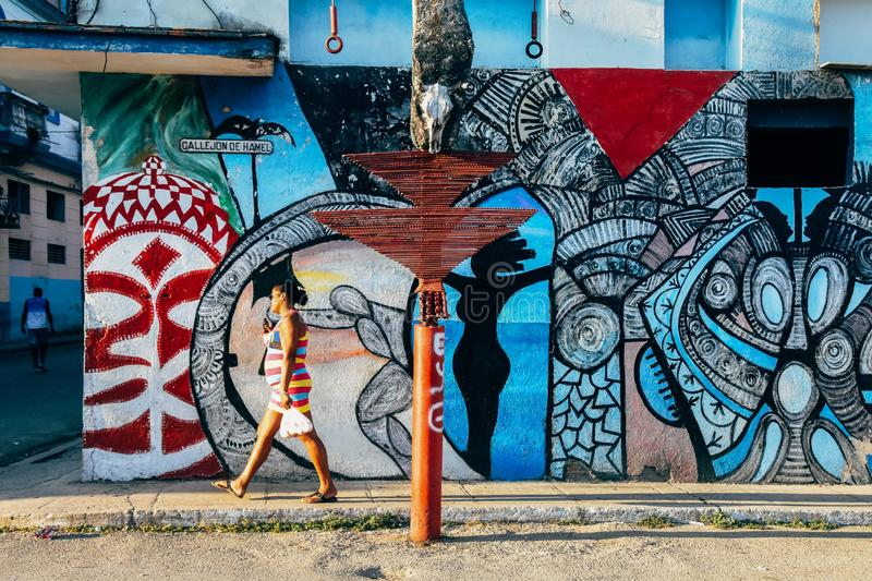 A colorful painted wall in Havana, Cuba. A local walks by a colorful painted wall in Havana, Cuba royalty free stock photography