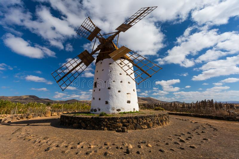 Local windmill, Lanzarote, Spain, Europe. Local, traditional windmill in a field with blue sky and green trees in background. Fuerteventura to Lanzarote, Spain royalty free stock image