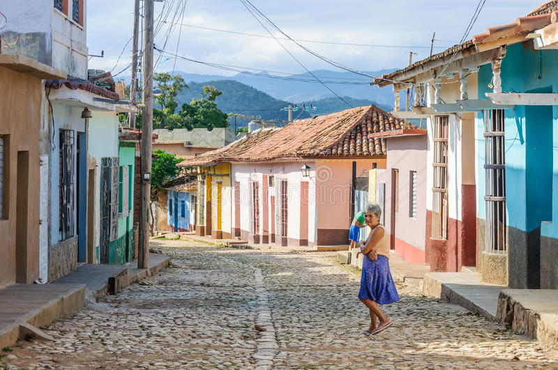 Local woman and colorful houses in Trinidad, Cuba royalty free stock images