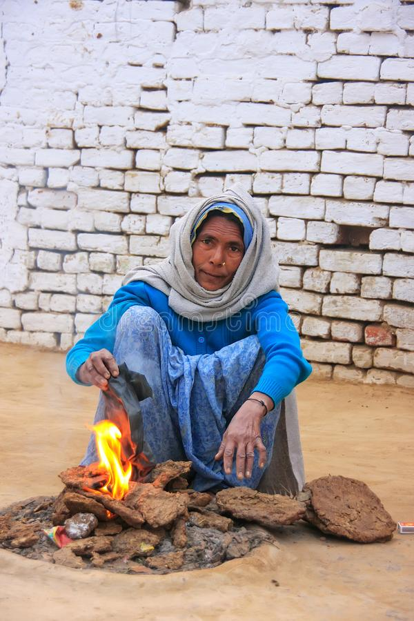 Local woman making fire using dry cow dung in Taj Ganj neighborhood of Agra, Uttar Pradesh, India. A disadvantage of using this kind of fuel is increased air stock image