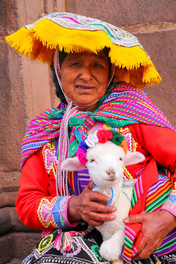 Local woman in traditional dress holding lamb in the street of C. Usco, Peru. In 1983 Cusco was declared a World Heritage Site by UNESCO royalty free stock image