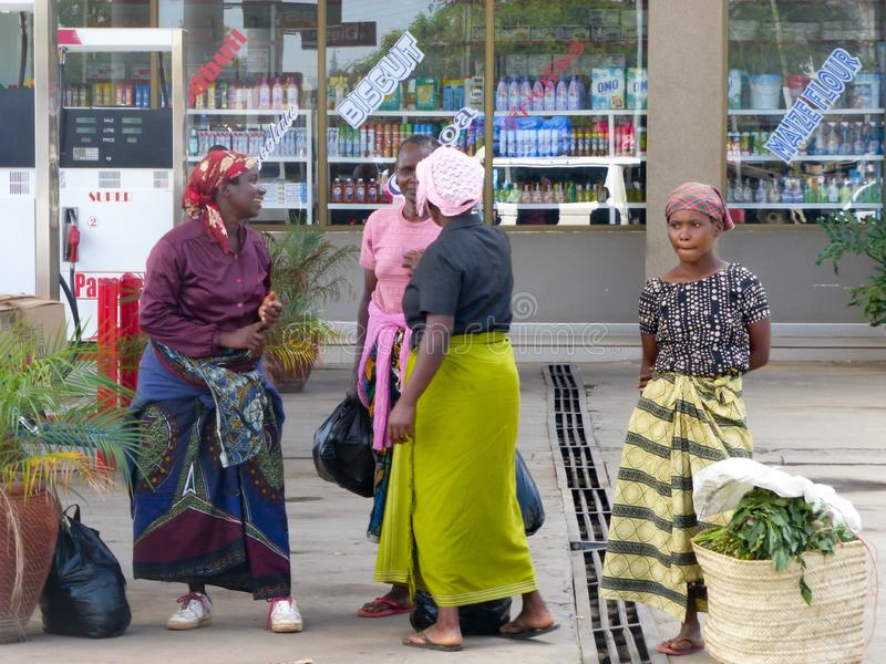 Local women wait at the bus stop and chat after coming from the daily market in the town center of Moshi. Moshi, Kilimanjaro Province / Tanzania: 28. December stock photos