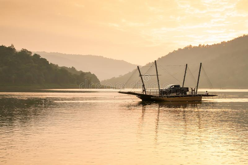 Local wooden ferry boat on peaceful lake at sunset. An asian man sits near pickup truck on the ferry boat, rural scene in Southeast Asia. Transportation stock image