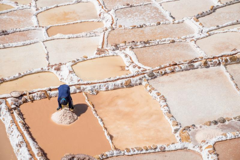 Local worker extracing salt from Maras salt mine, Urubamba, Cusco, Peru, South America royalty free stock image